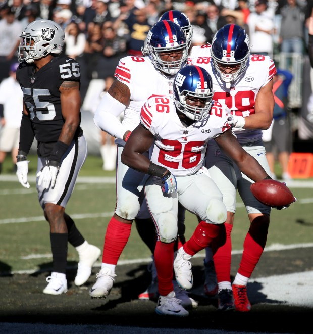 New York Giants running back Orleans Darkwa (26) celebrates his touchdown in the first quarter of their NFL game against the Oakland Raiders at the Coliseum in Oakland, Calif., on Sunday, Dec. 3, 2017. (Jane Tyska/Bay Area News Group)