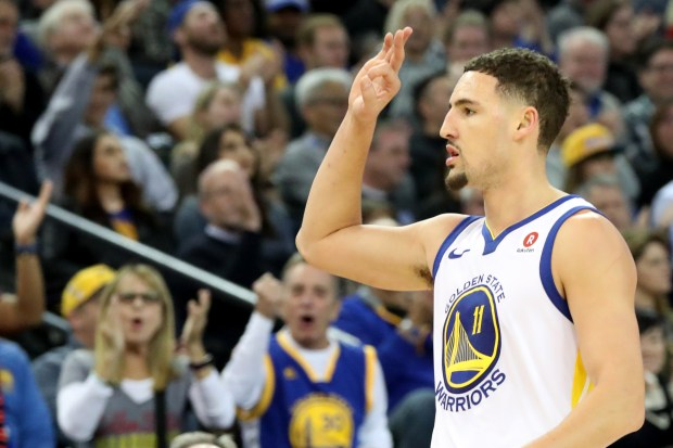 Golden State Warriors' Klay Thompson (11) celebrates a 3-point basket against the Dallas Mavericks in the second half of an NBA game at Oracle Arena in Oakland, Calif., on Thursday, Dec. 14, 2017. (Ray Chavez/Bay Area News Group)