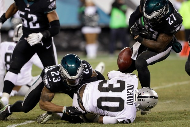 Oakland Raiders' Jalen Richard (30) fumbles the ball against Philadelphia Eagles' Rodney McLeod (23) and Malcolm Jenkins (27) during the second half of an NFL football game, Monday, Dec. 25, 2017, in Philadelphia. (AP Photo/Michael Perez)