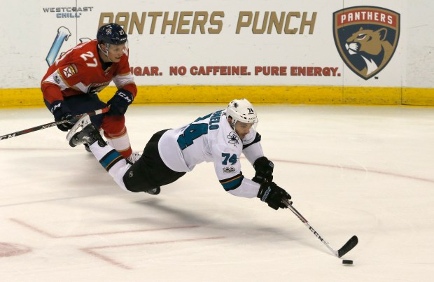 San Jose Sharks defenseman Dylan DeMelo (74) goes to the ice as Florida Panthers center Nick Bjugstad (27) pursues during the second period of an NHL hockey game, Friday, Dec. 1, 2017, in Sunrise, Fla. (AP Photo/Joe Skipper)