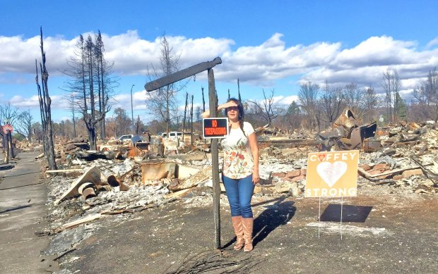 "Santa Rosa-based real estate agent Karen Maxwell stands next to what usedto be her ""for sale"" sign, in front of the burned remains of the CoffeyPark home she had listed for sale before the fire. (Courtesy of KarenMaxwell)"