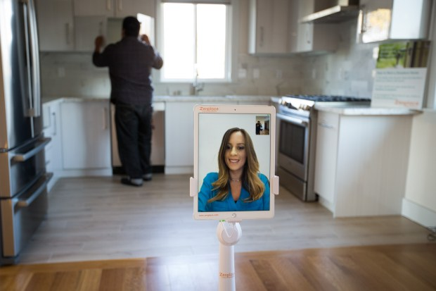 Zenplace agent Rabia Levy explains this two bedroom apartment to a potential tenant, Gilbert Serrano of San Jose, in Santa Clara on Dec. 7, 2017. Zenplace is using robots to guide prospective renters on tours of available homes. The robot is driven remotely by a real estate agent. (Dai Sugano/Bay Area News Group)