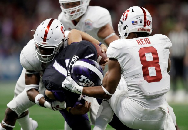 Stanford cornerback Quenton Meeks, left, and safety Justin Reid (8) pull down TCU quarterback Kenny Hill (7) on a short run during the first half of the Alamo Bowl NCAA college football game, Thursday, Dec. 28, 2017, in San Antonio. (AP Photo/Eric Gay)