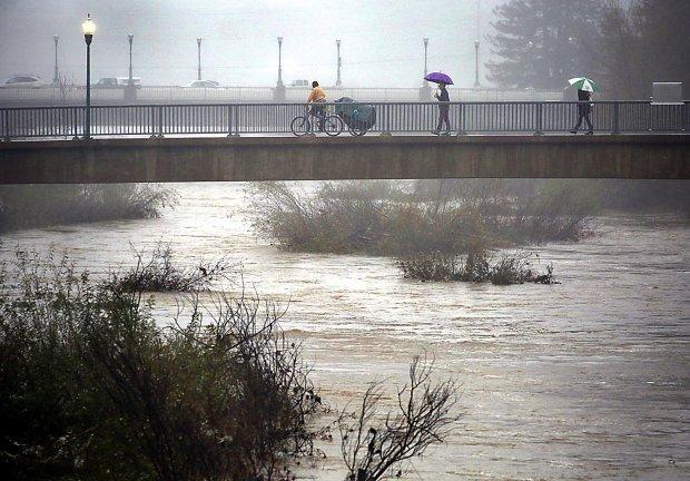 The rain-swollen San Lorenzo River flows through downtown Santa Cruz, California on Wednesday January 4, 2017. (Shmuel Thaler -- Santa Cruz Sentinel)