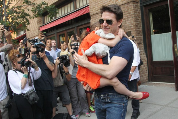 US actor Tom Cruise leaves his hotel carrying daughter Suri for her gymnastics class on July 17, 2012 in New York, NY. Fairytale Hollywood couple Tom Cruise and Katie Holmes last month announced they were calling it quits after five years of marriage, ending an unexpected love story dogged by tabloid rumors. AFP PHOTO / Mehdi Taamallah (Photo credit should read MEHDI TAAMALLAH/AFP/GettyImages)