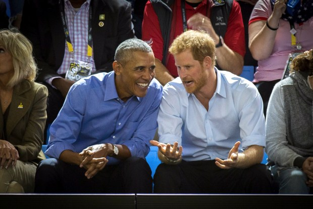 FILE - In this Friday, Sept. 29, 2017 file photo, former U.S. President Barack Obama, center left, and Britain's Prince Harry watch wheelchair basketball at the Invictus Games in Toronto. Former President Barack Obama told Prince Harry in an interview broadcast Wednesday, Dec. 27, 2017 that he felt serene the day he left the White House despite the sense that much important work remained unfinished. (Chris Donovan/The Canadian Press via AP, File)