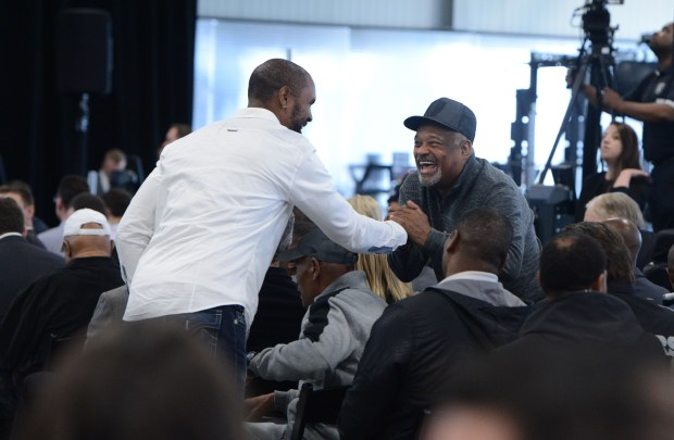 Former players, Charles Woodson, left, and George Atkinson, right, greet each other as the Oakland Raiders introduce Jon Gruden as their new head coach at the team facility in Alameda, Calif., on Tuesday, Jan. 9, 2018.(Dan Honda/Bay Area News Group)