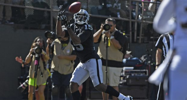 Oakland Raiders' Michael Crabtree (15) catches a touchdown pass thrown by Oakland Raiders quarterback EJ Manuel (3) in the second quarter of their NFL game at the Coliseum in Oakland, Calif. on Sunday, Oct. 8, 2017. (Jose Carlos Fajardo/Bay Area News Group)
