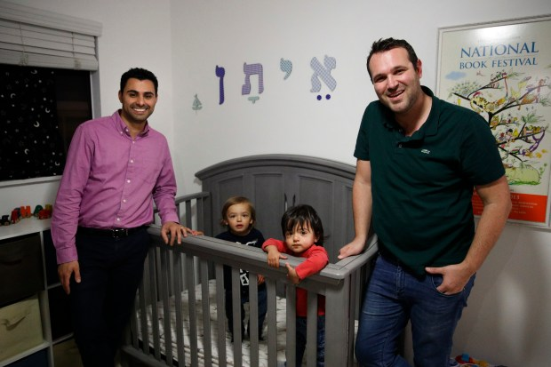 Elad Dvash-Banks, left, and his husband, Andrew, pose for photos with their twin sons, Ethan, center right, and Aiden in their apartment Tuesday, Jan. 23, 2018, in Los Angeles.  (AP Photo/Jae C. Hong)