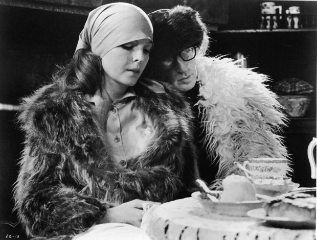 American actor Woody Allen leans his head on the shoulder of Diane Keaton in a scene from 'Love and Death,' directed by ALlen, 1975. Both wear furry coats and sit at a table. (Photo by United Artists/courtesy of Getty Images)