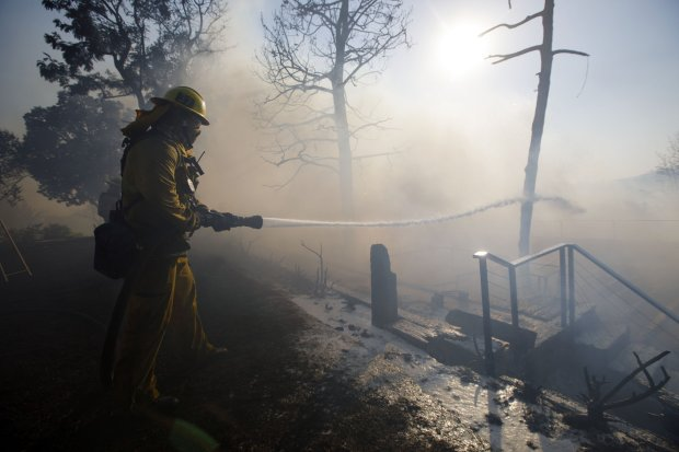 A firefighter hoses down a home's deck during the Skirball Fire in the BelAir neighborhood of Los Angeles on Dec. 6, 2017. MUST CREDIT: Bloomberg photo by Patrick T. Fallon.