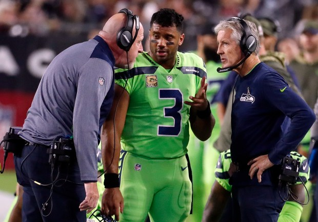 FILE - In this Thursday, Nov. 9, 2017, file photo, Seattle Seahawks quarterback Russell Wilson (3) speaks with head coach Pete Carroll, right, and assistant head coach Tom Cable during an NFL football game against the Arizona Cardinals in Glendale, Ariz. The Seahawks have been fined $100,000 for not properly following concussion protocol with Wilson during this game in November. The NFL and NFLPA announced their decision Thursday, Dec. 21, 2017, following an investigation that lasted more than a month.. (AP Photo/Rick Scuteri, File)