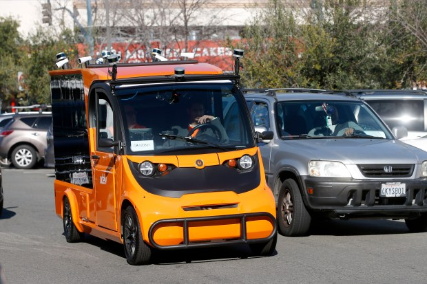 Udelv's autonomous delivery vehicle (with human backup driver in case of emergency) drives back to Draeger's market in San Mateo, Calif., Tuesday, Jan. 30, 2018, after making its initial grocery deliveries. (Karl Mondon/Bay Area News Group)