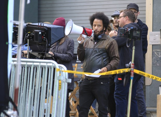 "Boots Riley yells directions on a megafone on Franklin Street in downtown Oakland, Calif., on Friday, July 14, 2017. Riley is making his director debut, shooting scenes throughout Oakland for the drama, ""Sorry to Bother You"". (Laura A. Oda/Bay Area News Group)"