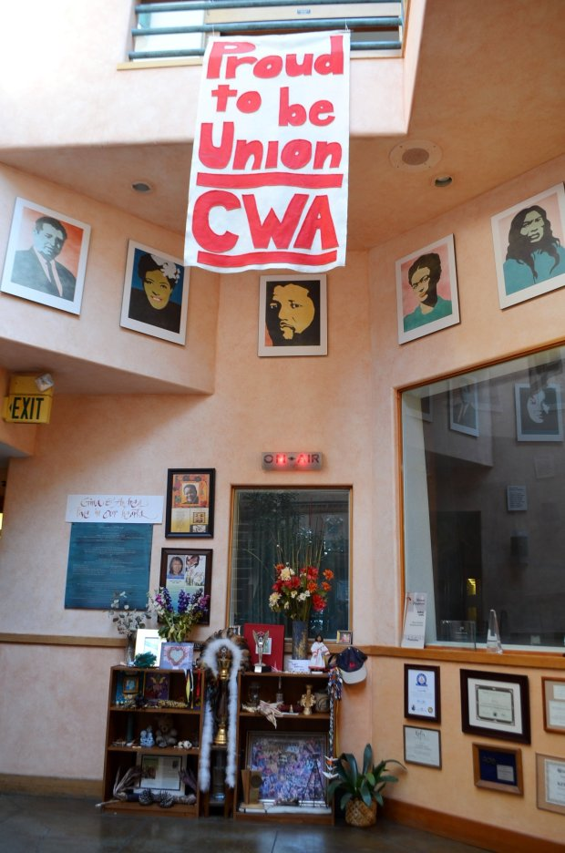 The atrium of KPFA in Berkeley, featured a union banner, posters ofprogressive leaders and a tribute to deceased radio hosts and guests. (Lisa M. Krieger)