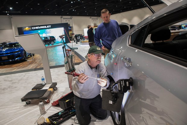 Joe Currin repairs small dents in a Chevy Volt in preparation for the opening of the Silicon Valley Auto Show at the San Jose McEnery Convention Center in San Jose, California on Wednesday, January 3, 2018. (LiPo Ching/Bay Area News Group)