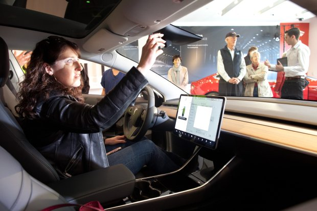 Annelies Lindemans, 47, of San Jose, a Tesla Model 3 reservation holder,adjusts the mirror on a display model of the car at the electric sedan's first appearance in a Tesla showroom, on Friday, Jan. 12 at Stanford Shopping Center in Palo Alto, Calif. (Ethan Baron/Bay Area News Group)