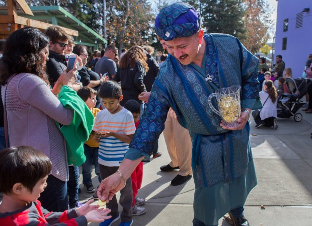 Martin Sanchez hands out candy coins as he portrays one of the Three Kings at the Children's Discovery Museum in San Jose, California, Saturday, Jan. 6, 2018. The museum hosted a celebration in honor of El Dia de los Tres Reyes Magos, or The Three Kings. (Patrick Tehan/Bay Area News Group)