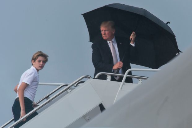 US President Donald Trump holds an umbrella as he waits for his son Barron and wife Melania to board Air Force One at Palm Beach International Airport in West Palm Beach, Florida on January 12, 2018.Trump is returning to Washington, DC after spending the weekend in Florida. / AFP PHOTO / Nicholas Kamm (Photo credit should read NICHOLAS KAMM/AFP/Getty Images)