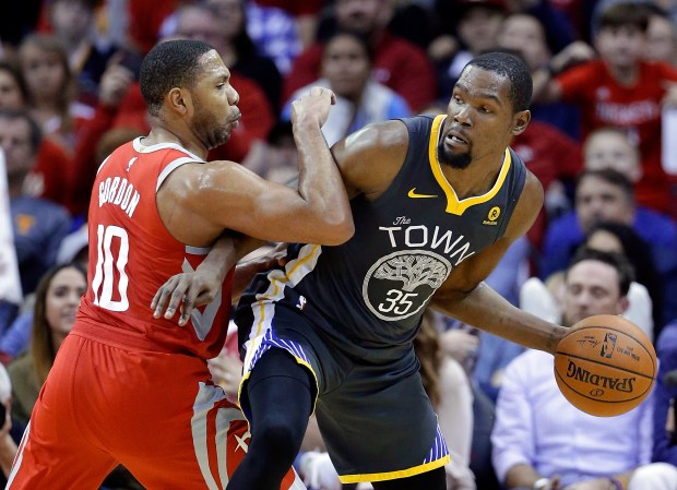 Golden State Warriors forward Kevin Durant (35) looks to pass the ball under pressure from Houston Rockets guard Eric Gordon (10) during the second half of an NBA basketball game Saturday, Jan. 20, 2018, in Houston. (AP Photo/Michael Wyke)