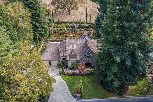 This .4-acre lot comes with redwood trees at the corners and backs up to open space with an oak tree and Italian cypresses.