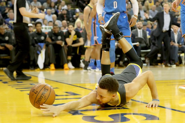 Golden State Warriors' Stephen Curry (30) hits the floor after he drove past Oklahoma City Thunder's Russell Westbrook (0) in the first half of an NBA game at Oracle Arena in Oakland, Calif., on Tuesday, Feb. 6, 2018. (Ray Chavez/Bay Area News Group)