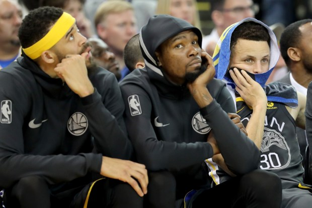 Golden State Warriors' JaVale McGee (1), Kevin Durant (35) and Stephen Curry (30) sit in the bench as Oklahoma City Thunder wins in the second half of an NBA game at Oracle Arena in Oakland, Calif., on Tuesday, Feb. 6, 2018. (Ray Chavez/Bay Area News Group)