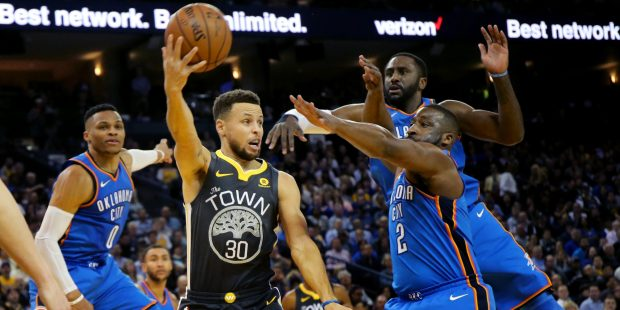 Golden State Warriors' Stephen Curry (30) passes the ball under the basket against Oklahoma City Thunder's Russell Westbrook (0) in the first half of an NBA game at Oracle Arena in Oakland, Calif., on Tuesday, Feb. 6, 2018. (Ray Chavez/Bay Area News Group)