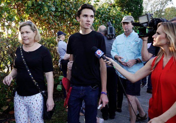 Student David Hogg speaks to the media as he returns to Marjory Stoneman Douglas High School in Parkland, Fla., Wednesday, Feb. 28, 2018. With a heavy police presence, classes resumed for the first time since several students and teachers were killed by a former student on Feb. 14. (Joe Cavaretta/South Florida Sun-Sentinel via AP)