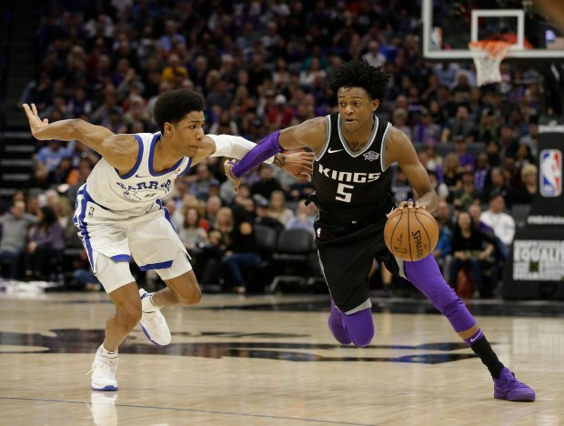 Sacramento Kings guard De'Aaron Fox, right, drives against Golden State Warriors guard Patrick McCaw during the second half of an NBA basketball game Friday, Feb. 2, 2018, in Sacramento, Calif. The Warriors won 119-104. (AP Photo/Rich Pedroncelli)