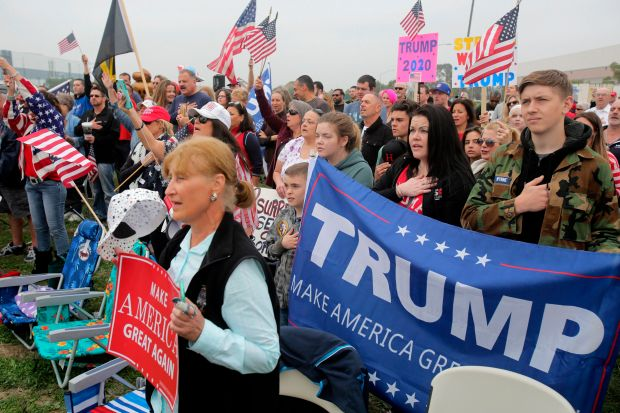 Trump supporters sing the National Anthem and display pro-Trump signs during a pro-Trump rally attended by about 500 people in San Diego, California, March 13, 2017, where President Trump was visiting the nearby border wall protoypes. / AFP PHOTO / Bill WechterBILL WECHTER/AFP/Getty Images