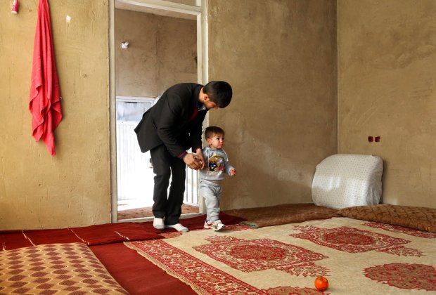 Asadullah Poya with his 18-month-old son Donald Trump, arrive for interview with The Associated Press at their rented house in Kabul, Afghanistan, Thursday, March 15, 2018. Poya, from a small, rural village, named his newborn son Donald Trump, hoping it would bring the boy good fortune. It hasn't. Relatives and neighbors were furious that he broke with tradition and gave his son a non-Muslim name. He was forced to move his family to Kabul, and they've received death threats online. (AP Photo/Rahmat Gul)