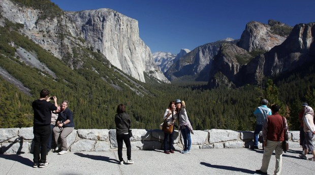 FILE - In this Oct. 17, 2013, file photo, visitors at Tunnel View, like Kaori Nishimura and Eriko Kuboi, from Japan, center facing, enjoy the views of Yosemite National Park, Calif. Tunnel View is a scenic vista which shows off El Capitan, Half Dome and Bridalveil Fall. (AP Photo/Gary Kazanjian, File)