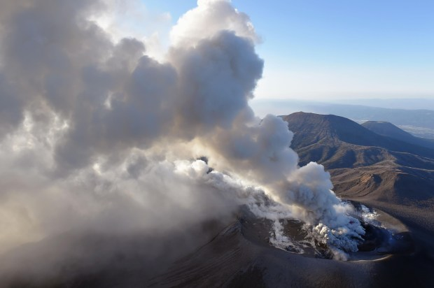 A column of volcanic smoke rises from the crater on the Shinmoedake volcano after its eruption in Kirishima, southern Japan, Tuesday, March 6, 2018. The volcano erupted violently several times Tuesday, shooting up ash and smoke up to 2,300 meters (7,500 feet) in its biggest explosion since 2011, the Meteorological Agency said. (Kyodo News via AP)