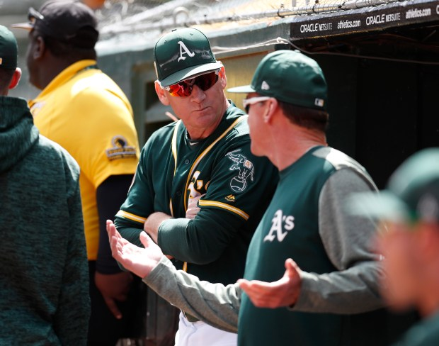 Oakland Athletics third base coach Matt Williams talks to Oakland Athletics manager Bob Melvin before their game against the San Francisco Giants at the Oakland Coliseum in Oakland, Calif., on Sunday, March 25, 2018. (Nhat V. Meyer/Bay Area News Group)