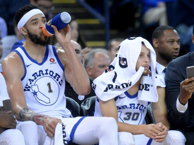 Golden State Warriors' Stephen Curry (30) sits next to Golden State Warriors' JaVale McGee (1) in the second period of their NBA game against the Atlanta Hawks at Oracle Arena in Oakland, Calif., on Friday, March 23, 2018. (Doug Duran/Bay Area News Group)