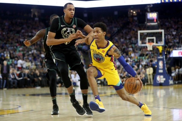 Patrick McCaw of Golden State Warriors (0) drives John Henson (31) of Milwaukee Bucks in the first half of an NBA game at the Oracle Arena in Oakland, California, Thursday, March 29, 2018. (Ray Chavez / Bay Area Newsgroup)