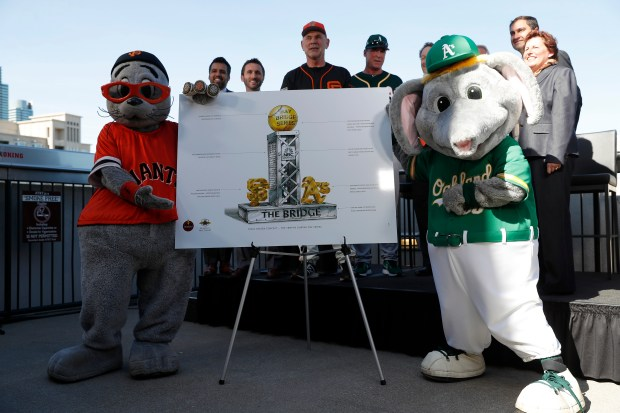 San Francisco Giants mascot Lou Seal and Oakland Athletics mascot Stomper pose for pictures with the new Bay Bridge Series trophy rendering with San Francisco Giants manager Bruce Bochy and Oakland Athletics manager Bob Melville at AT&T Park in San Francisco, Calif., on Monday, March 26, 2018. (Nhat V. Meyer/Bay Area News Group)