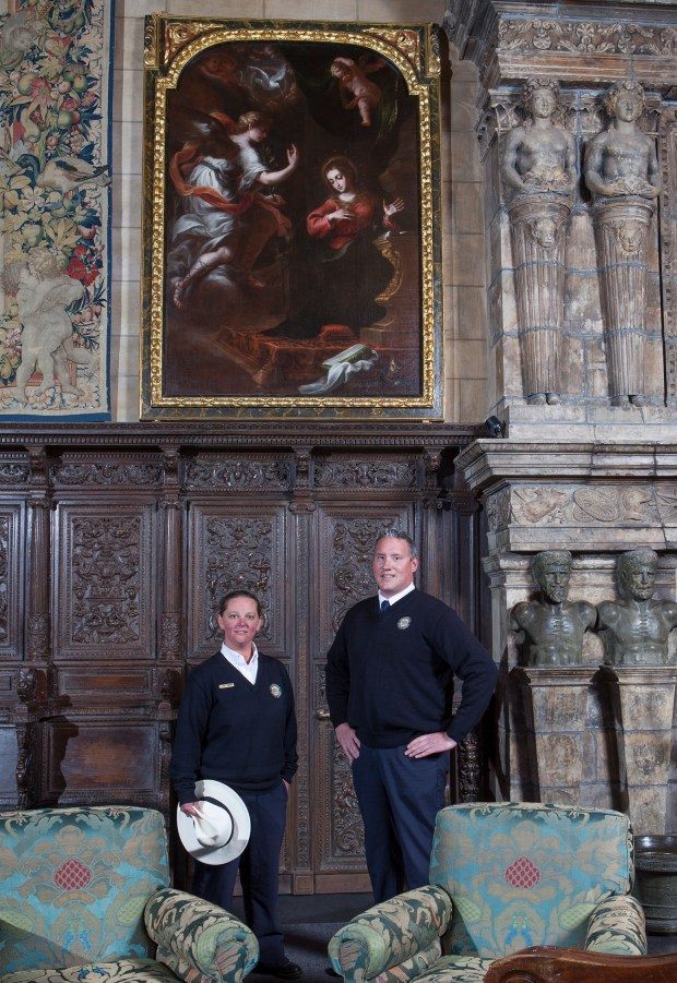 """Guides Laurel Rodger and Carson Cargill pose below the """"Annunciation"""" painting hanging at Hearst Castle in San Simeon, Calif.  (Victoria Garagliano/Hearst Castle/California State Parks via AP)"""
