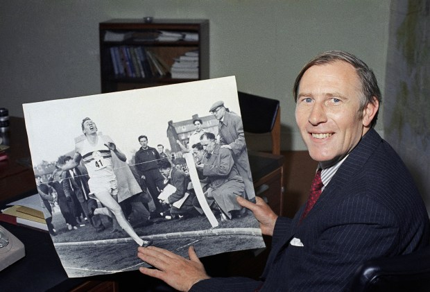 1974 photo: Roger Bannister, then 45, displays a photo of him made at Iffley, England on May 6, 1954 when he smashed the four-minute-mile barrier.(AP Photo/File)