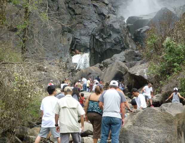 Crowds of Yosemite National Park patrons at Bridalveil Fall in July 2017, before a capital campaign restoration project was completed there. Yosemite officials are putting the final touches on a $13 million restoration plan of the area, with half the funding coming from a Bay Area non-profit group, the Yosemite Conservancy. The new plan will feature a larger parking lot, modern flush toilets, interpretive signs and wider hiking trails with wooden boardwalks and more accessible features designed in the classic granite and pine national park style. The project will begin in the spring of 2019 and be completed a year later. (Courtesy Karen Hockett/National Park Service)