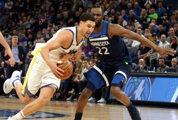 Golden State Warriors' Klay Thompson drives around Minnesota Timberwolves' Andrew Wiggins in the second half of an NBA basketball game Sunday, March 11, 2018, in Minneapolis. The Timberwolves won 109-103. Thompson scored 21 points and Wiggins scored 23. (AP Photo/Jim Mone)