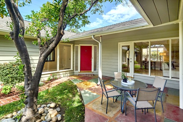 This home on University Way is built around a central courtyard with a mature orange tree, brick outdoor fireplace, lawn and covered patio.