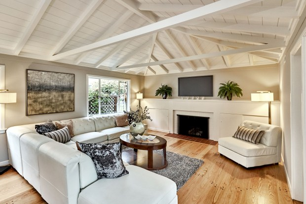 The living room is light and airy with painted crown molding, exposed beams and a vaulted ceiling.