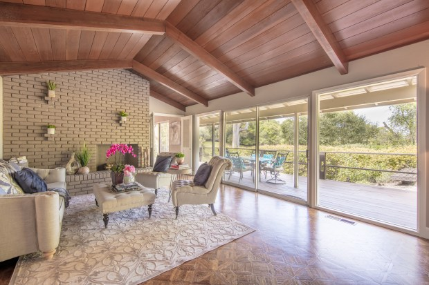 This home in Ladera features hardwood floors, soaring exposed-beam ceilings, and a wall of windows in the dining and living rooms.