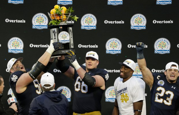 Notre Dame players, from left, Quenton Nelson, Mike McGlinchey, Miles Boykin and Drue Tranquill celebrate with the championship trophy after defeating LSU 21-17 in the Citrus Bowl NCAA college football game, Monday, Jan. 1, 2018, in Orlando, Fla. (AP Photo/John Raoux)