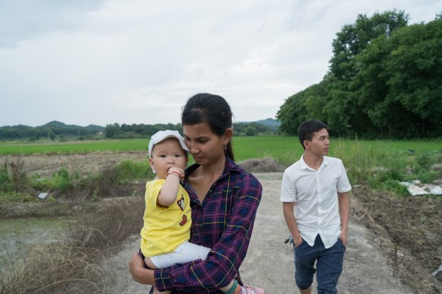 Sreynich Yorn, holding her 9-month-old daughter, walks in the village withher husband Liu Hua in Leping, China, in 2017. The couple got married in May 2013, and have a son and a daughter. Liu works as a carpenter and house painter in Guangzhou, while Yorn and her mother-in-law stay at home to take care of the two kids. MUST CREDIT: Photo for The Washington Post by Yan Cong