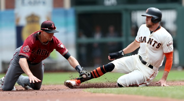 San Francisco Giants' Hunter Pence (8) is tagged out by Arizona Diamondbacks shortstop Nick Ahmed (13) in the third inning of their MLB game at AT&T Park in San Francisco, Calif., on Wednesday, April 11, 2018. (Jane Tyska/Bay Area News Group)