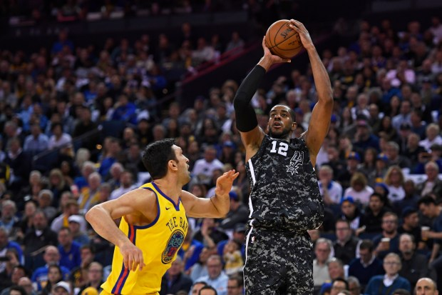 San Antonio Spurs' LaMarcus Aldridge (12) shoots over Golden State Warriors' Zaza Pachulia (27) during the third quarter of their NBA game at the Oracle Arena in Oakland, Calif., on Thursday, March 8, 2018. The Golden State Warriors defeated the San Antonio Spurs 110-107. (Jose Carlos Fajardo/Bay Area News Group)