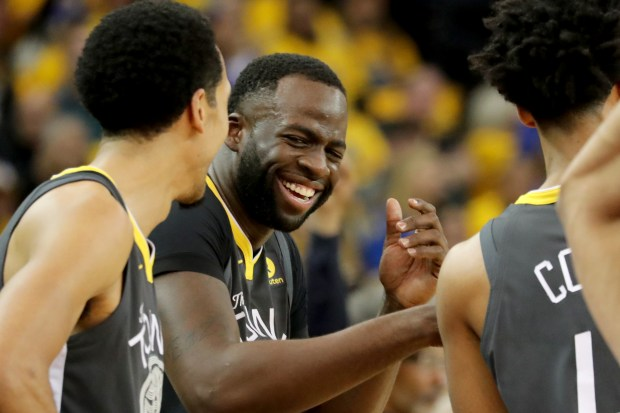 Golden State Warriors' Shaun Livingston (34) and Draymond Green (23) share a laugh after a timeout against the San Antonio Spurs during the second quarter of Game 2 of their NBA first-round playoff series at Oracle Arena in Oakland, Calif., on Monday, April 16, 2018.(Ray Chavez/Bay Area News Group)